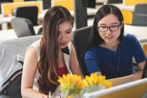 shallow focus photography of two women doing work in table